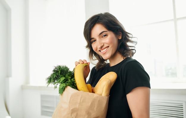 Брюнетка в черных футболках с продуктами, покупками здоровой пищи