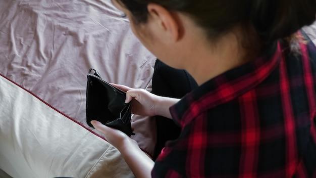 침대에 빈 검은색 지갑이 있는 체크 무늬 셔츠를 입은 갈색 머리 뒷면 위쪽 보기