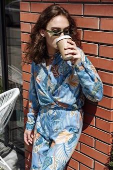 안경 모델 여자의 갈색 머리 옷과 마시는 커피 초상화의 새로운 컬렉션에서 포즈