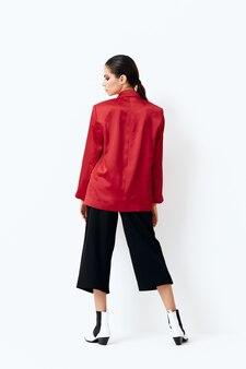 Брюнетка в стильной одежде стоит назад мода позирует изолированной стене.