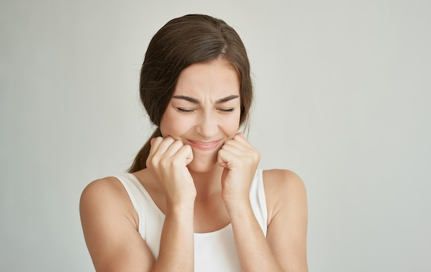 Брюнетка в белой футболке проблемы с зубами недовольство серым