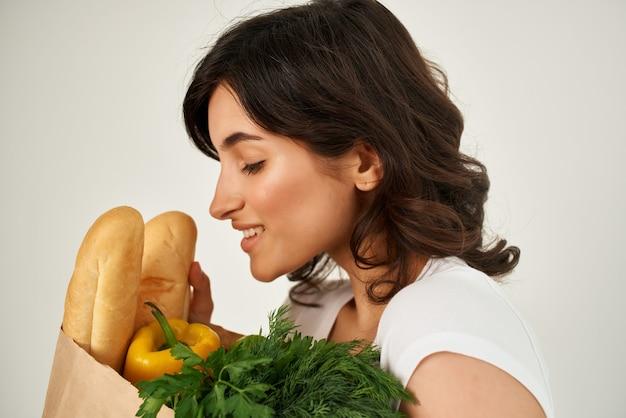 食料品の健康的な食品配達のクローズアップと白いtシャツパッケージのブルネット