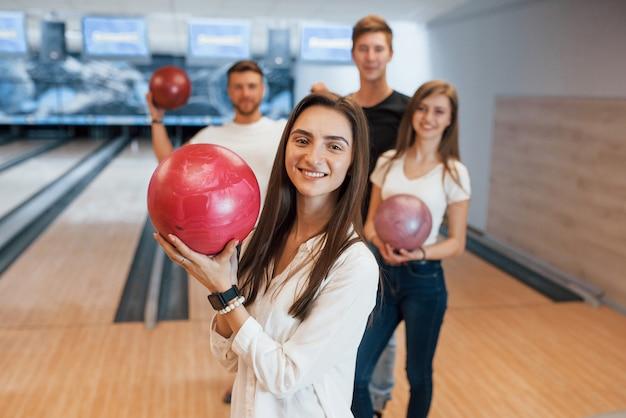 Brunette è felice di essere lì. i giovani amici allegri si divertono al bowling durante i fine settimana