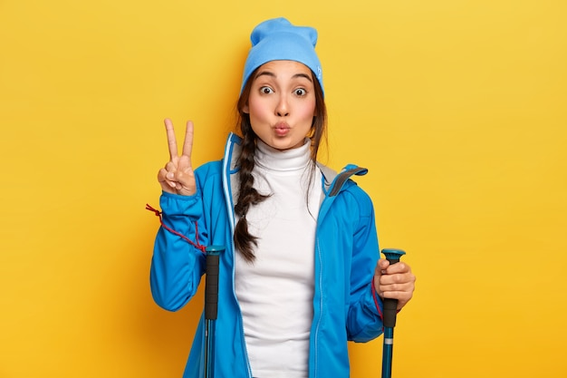 Brunette korean woman makes peace gesture, hikes in forest, holds trekking poles, dressed in blue casual clothes, enjoys active rest, poses over yellow wall