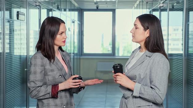 灰色のジャケットを着たブルネットの女性の成功した会社のマネージャーは、プロジェクトについて話し合い、大きな窓に対して廊下に立って満足してハイタッチをします