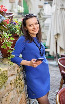 Brunette lady in blue dress with a smartphone