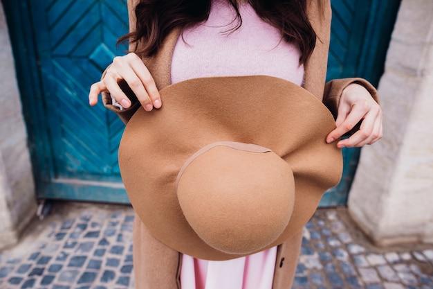 Signora bruna tiene il cappello beige prima del suo vestito