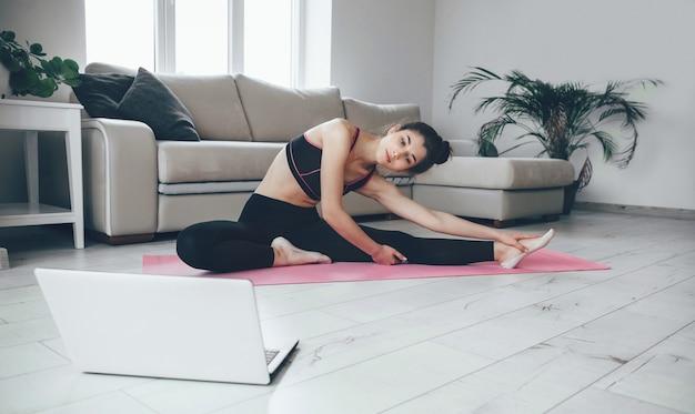 ラップトップを見て、ヨガの練習をしている床にストレッチスポーツウェアのブルネットの女性