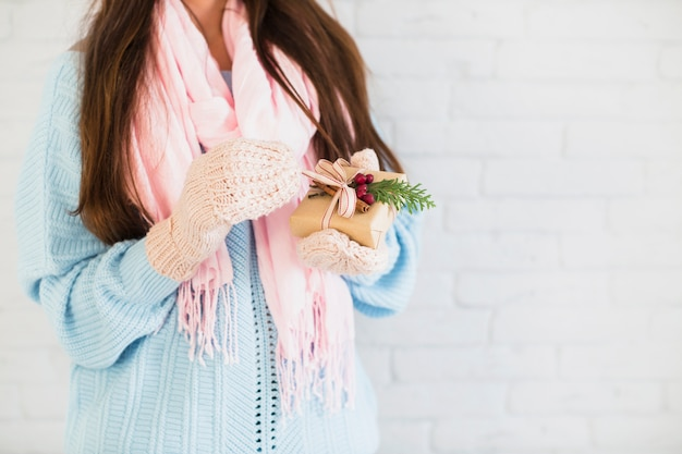 Brunette lady in mittens and scarf with gift box in hands