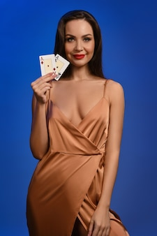 Brunette lady in silk golden dress she is smiling showing two playing cards posing on blue wall
