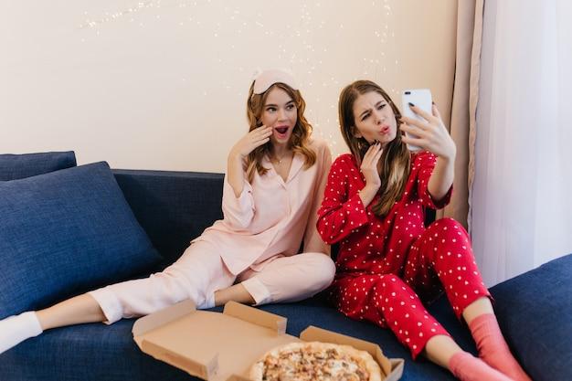 갈색 머리 아가씨는 친구와 함께 셀카를 위해 전화를 사용하고 재미있는 얼굴을 만듭니다. 함께 피자를 먹는 귀여운 잠옷 두 자매의 실내 사진.