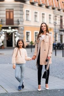 Брюнетка дама гуляет со своей красивой дочерью на фоне улицы в осенний день.