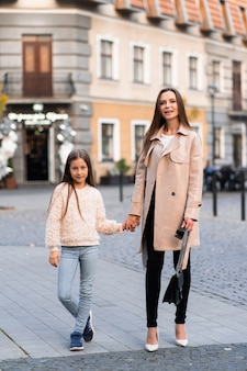 Brunette lady walking with her beautiful daughter on street background in autumn day.