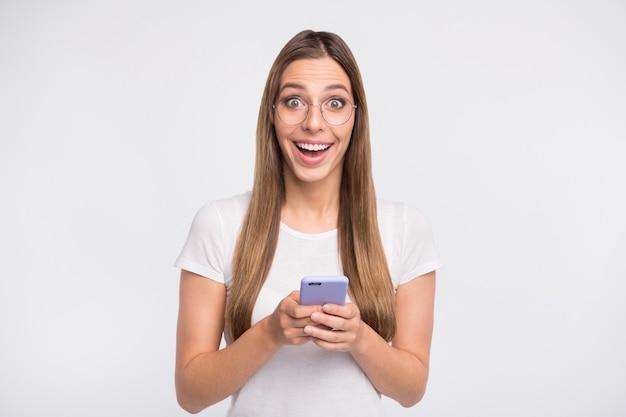 Брюнетка дама в очках позирует на белой стене со своим телефоном