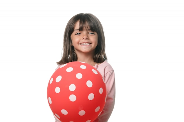Brunette little girl smiling to camera with a balloon on white background