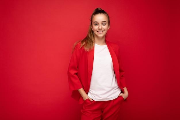 トレンディな赤いジャケットと白いtシャツを身に着けているブルネットの少女は、カメラを見て赤い背景の壁の上に孤立して立っているモックアップ。フリースペース