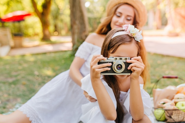 週末を楽しんでいる自然の写真を撮る髪のリボンとブルネットの少女。彼女の娘がカメラを持っている公園で魅力的な若い女性の屋外の肖像画。