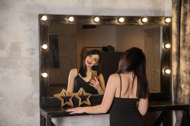 Brunette in a loft interior in the reflection of the mirror takes pictures of herself