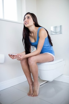 Brunette looking at her pregnant test in toilet