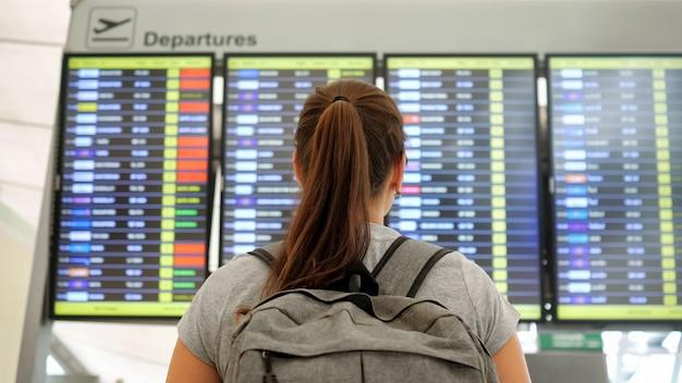 Брюнетка смотрит на расписание вылетов в терминале аэропорта