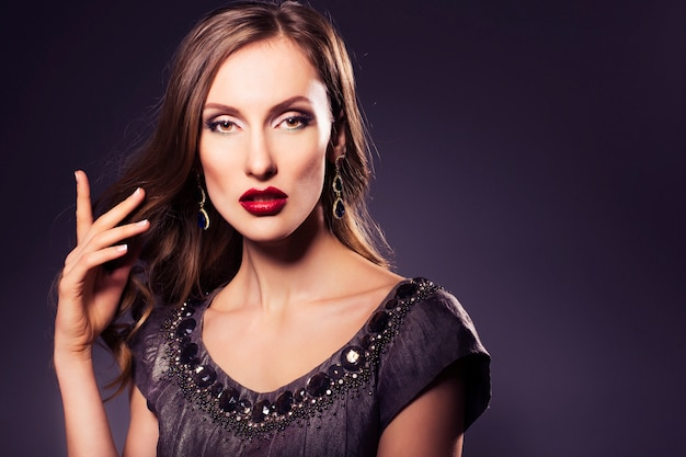 Brunette luxury woman in dress with clear skin and evening dark make up: green cat eye and brown eyeshadows. waved hairstyle. dark background. copy space