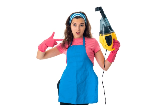 Brunette maid woman in an apron with cleansers isolated on white wall