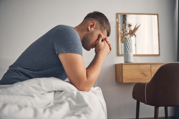 Brunette male in blue t-shirt sitting on the bed in cosy atmosphere while closing his eyes with hands