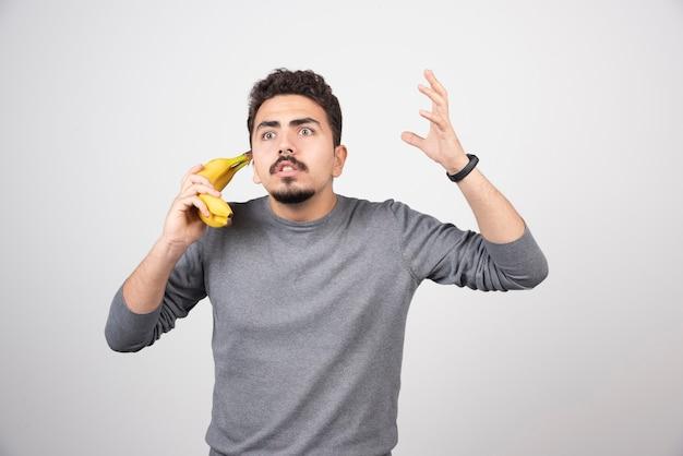 Брюнетка мужчина держит банан как телефон.