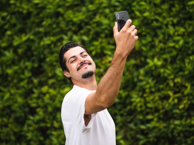 Maschio brunetta che si fa i selfie contro una vegetazione