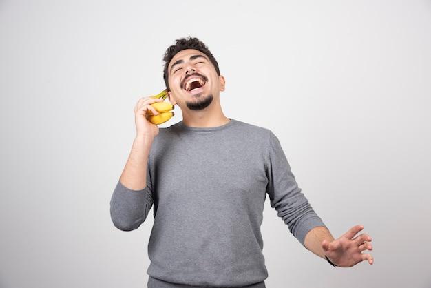Брюнетка мужчина разговаривает с бананом на сером.