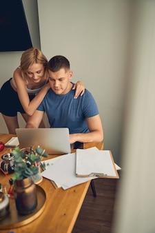 귀여운 젊은 여자가 포옹하고 그를 보는 동안 집에서 노트북에서 일하는 갈색 머리 남성