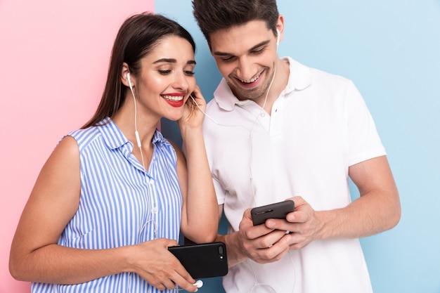 Брюнетка мужчина и женщина в наушниках и с помощью смартфонов, изолированные на красочной стене
