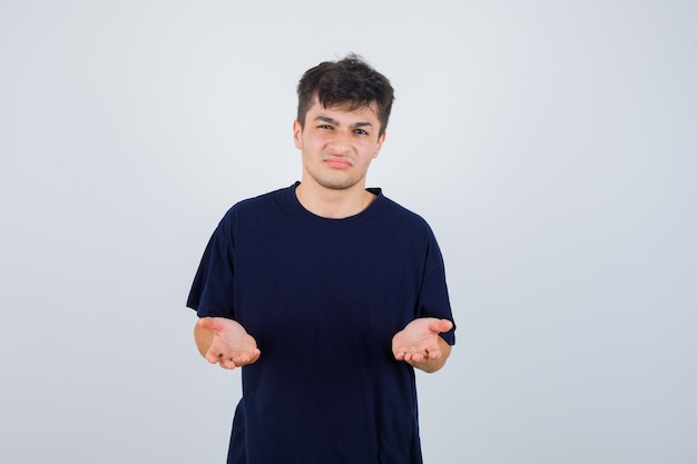 Brunette man being displeased with dumb question in dark t-shirt and looking gloomy, front view.
