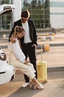 Uomo castana in abito nero e maglietta bianca abbraccia la sua ragazza bionda