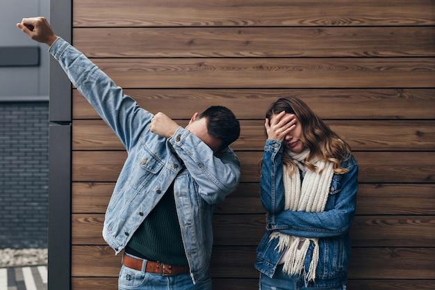 Uomo castana in abbigliamento denim scherzare sulla parete di legno. ragazza stanca in sciarpa lavorata a maglia lunga che copre gli occhi con la mano.