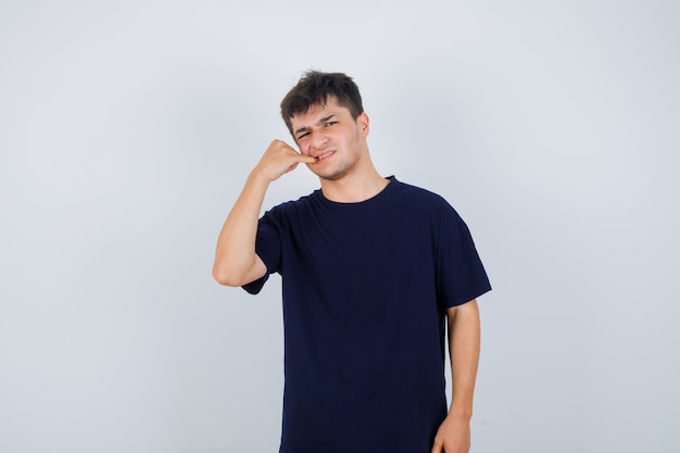 Brunette man holding finger in mouth in dark t-shirt and looking dissatisfied , front view.