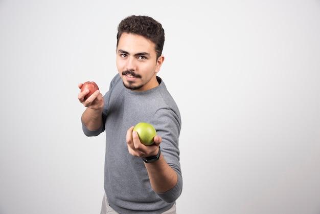 Uomo castana che tiene mele verdi e rosse.