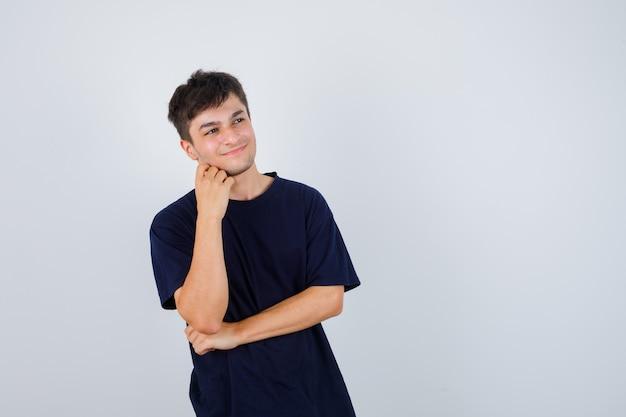 Uomo castana che tiene la mano sul mento in maglietta e che sembra soddisfatto. vista frontale.