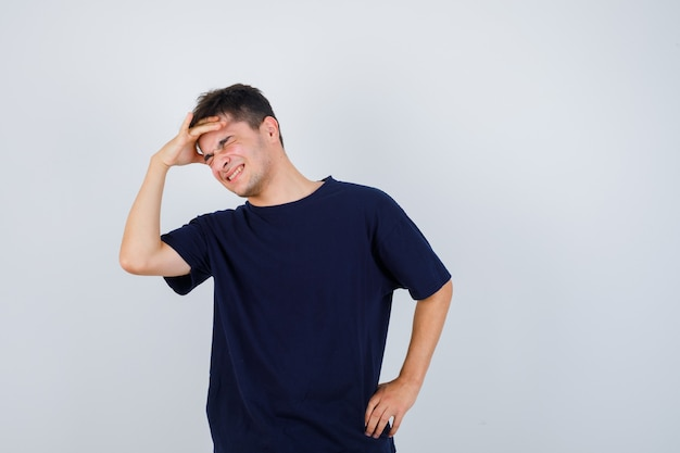 ブルネットの男がtシャツを着て頭上に手をつないでうれしそうに見えます。正面図。
