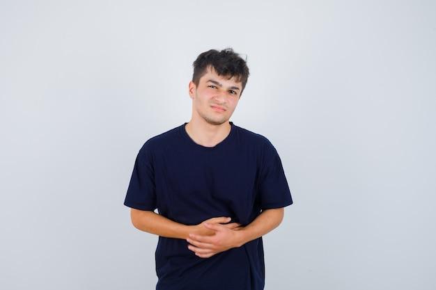 Брюнетка мужчина держит руки на животе в темной футболке и выглядит болезненно, вид спереди.