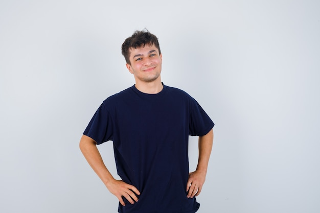 Uomo castana che tiene le mani sulla vita in maglietta scura e che sembra bello, vista frontale.