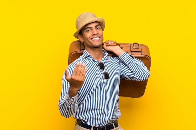 Brunette man holding a vintage briefcase over isolated yellow wall inviting to come with hand. happy that you came