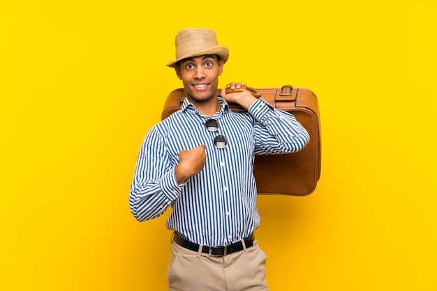 Brunette man holding a vintage briefcase over isolated yellow with surprise facial expression