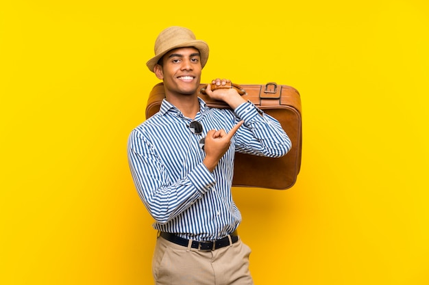 Brunette man holding a vintage briefcase over  yellow wall pointing to the side to present a product