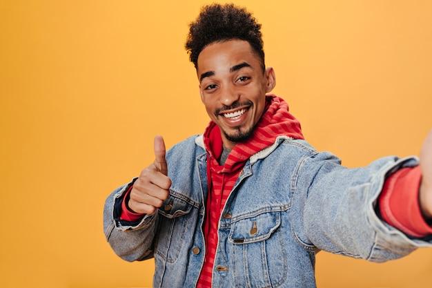 L'uomo castana in felpa con cappuccio e giacca di jeans mostra il pollice in su e fa selfie