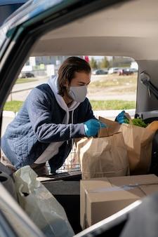 Брюнетка в маске и перчатках загружает продукты из супермаркета в багажник автомобиля после покупок во время пандемии