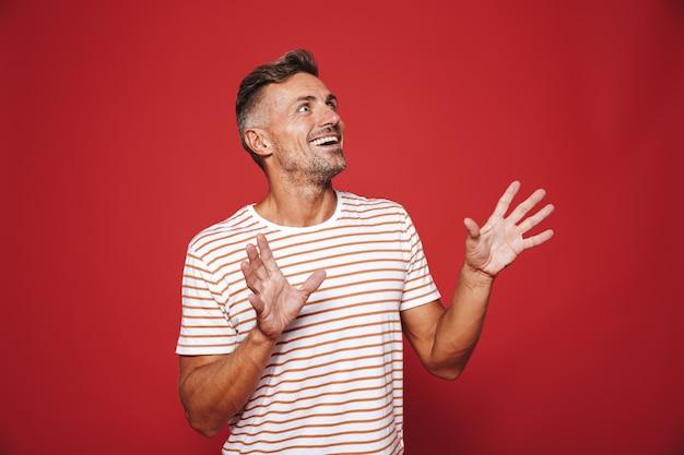Брюнетка в полосатой футболке радуется и смотрит в сторону на copyspace, изолированное на красном
