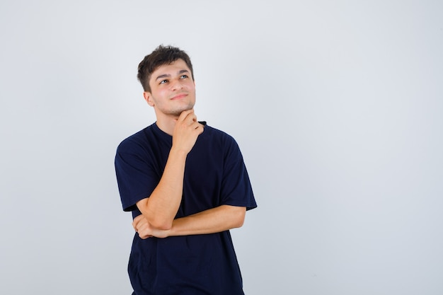 Брюнетка мужчина в футболке держит руку под подбородком и смотрит вдумчивый, вид спереди.