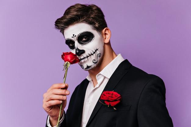 할로윈에 장미와 함께 포즈 턱시도에 갈색 머리 남자. 보라색 배경에 서있는 멕시코 무서운 화장과 잘 생긴 남성 모델.