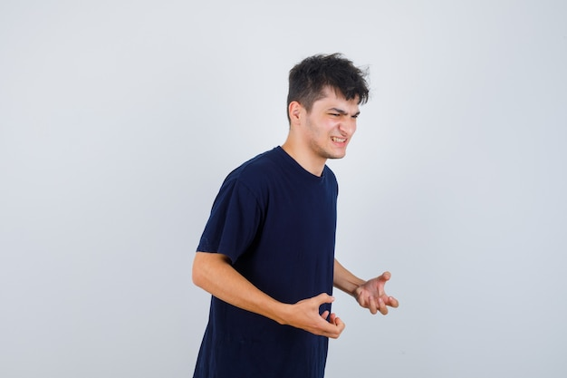 Brunette man keeping hands in aggressive manner in t-shirt and looking annoyed. front view.